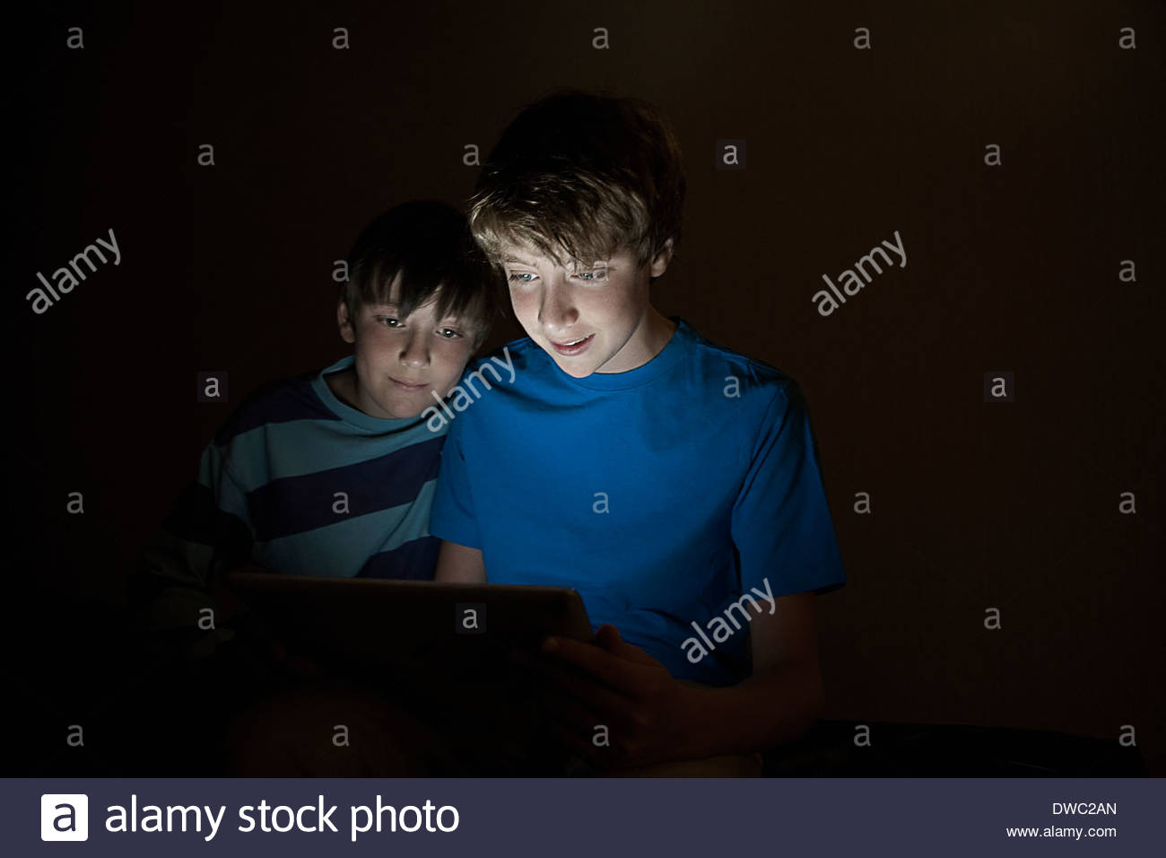 Teenage boy and brother looking at digital tablet at night - Stock Image