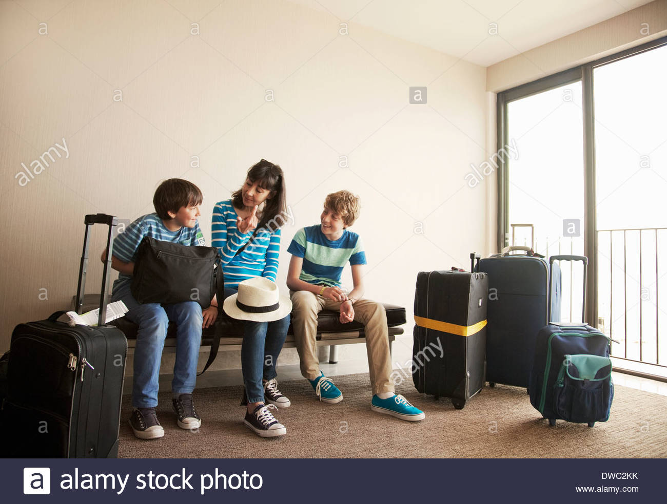 Mother and two sons with wheeled cases at airport - Stock Image