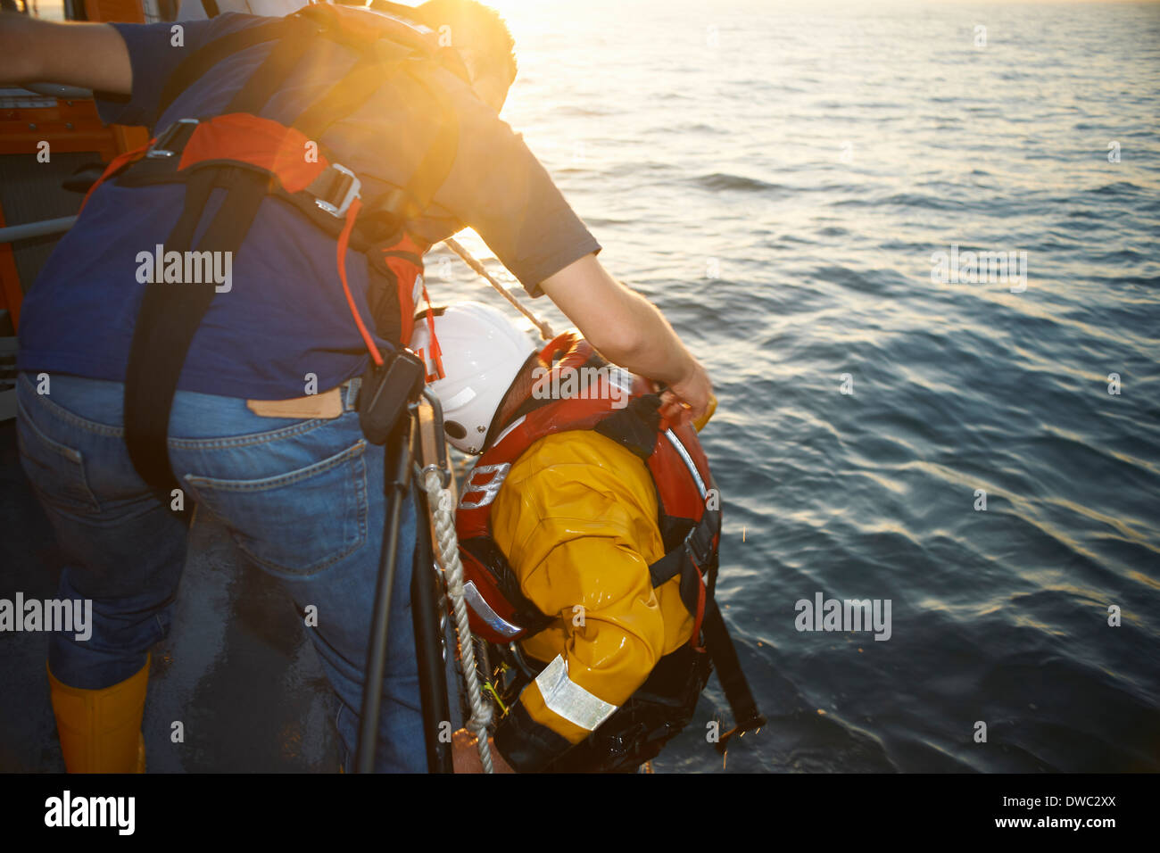 Lifeboat crew training and pulling up team member from sea - Stock Image