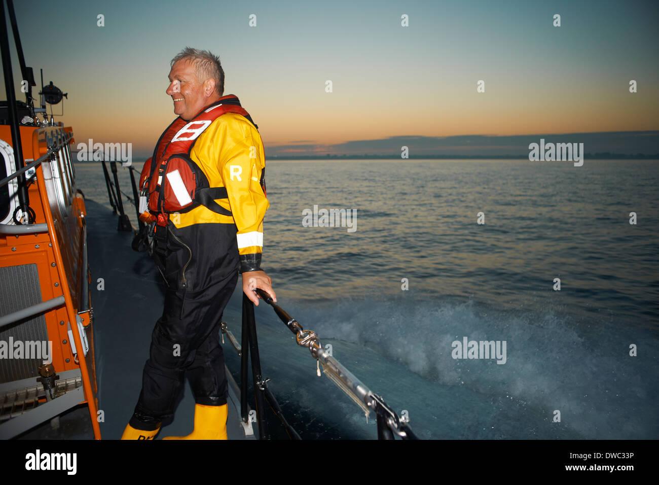Portrait of mature man holding lifeboat railing at sea Stock Photo