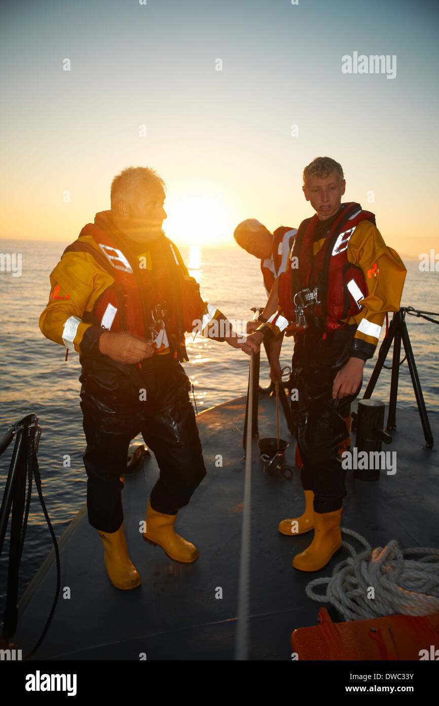 Portrait of three men holding lifeboat railing at sea Stock Photo