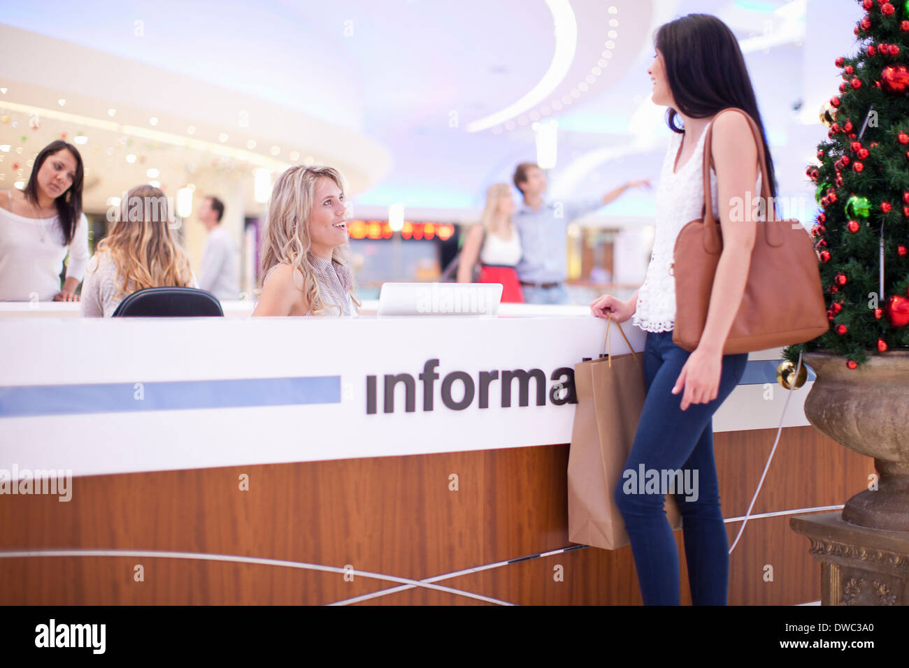 Young woman at information desk in mall - Stock Image