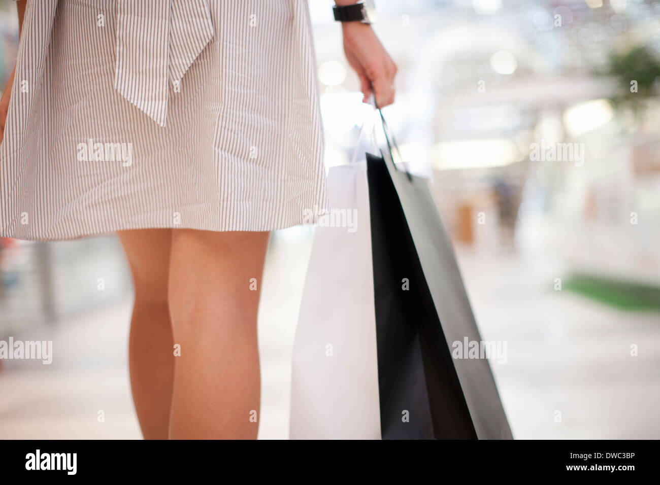Backview of young woman with shopping bag - Stock Image