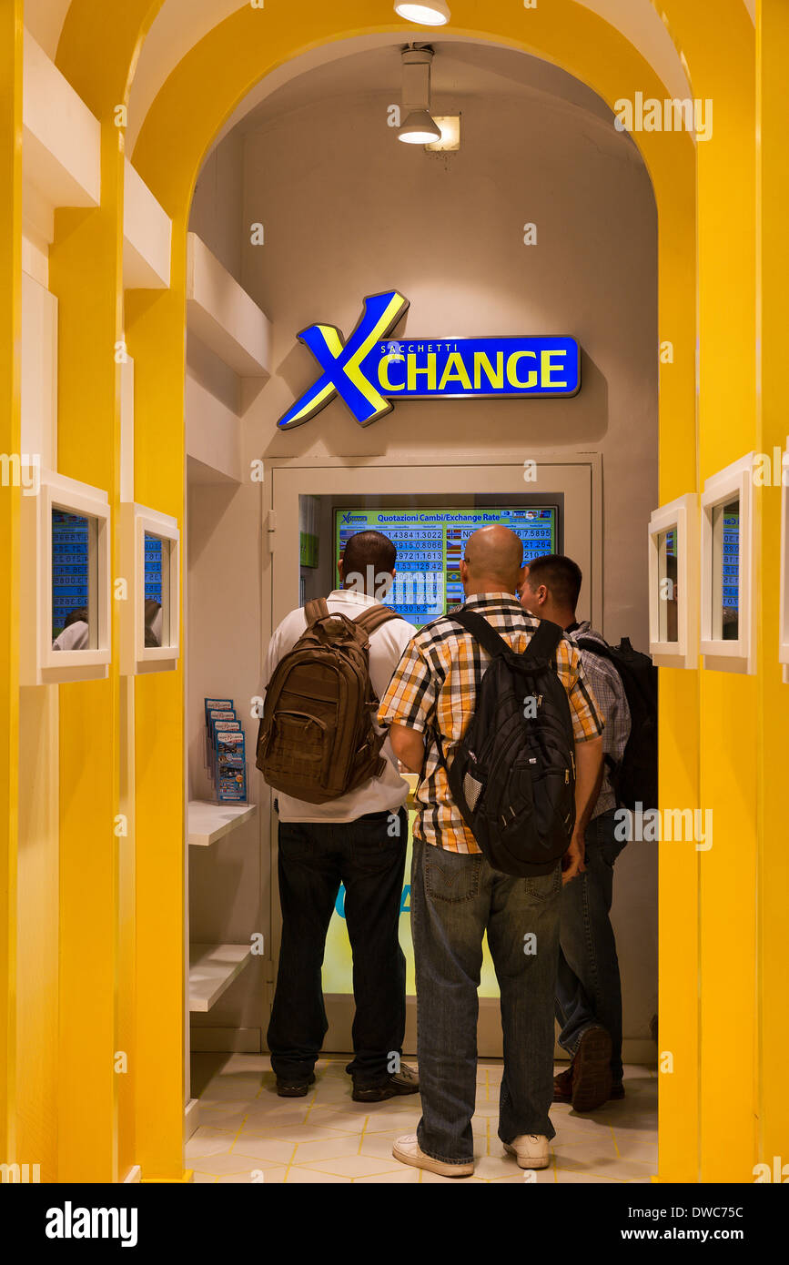 Young travelers exchange currency at an automated exchange booth, Rome, Italy. - Stock Image