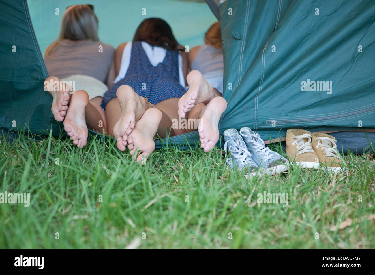 Three young females friends feet at tent entrance - Stock Image