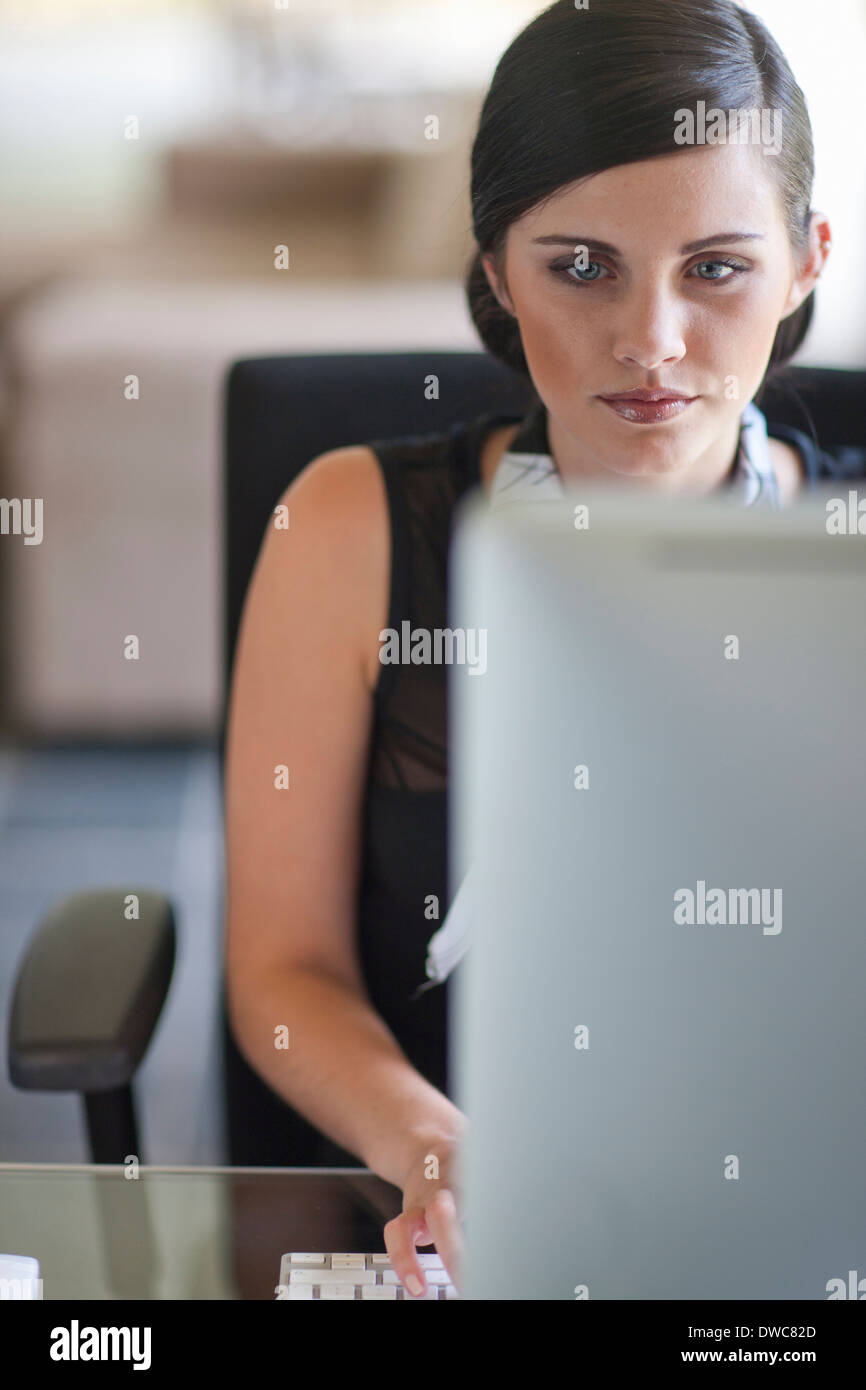 Young office worker using computer - Stock Image