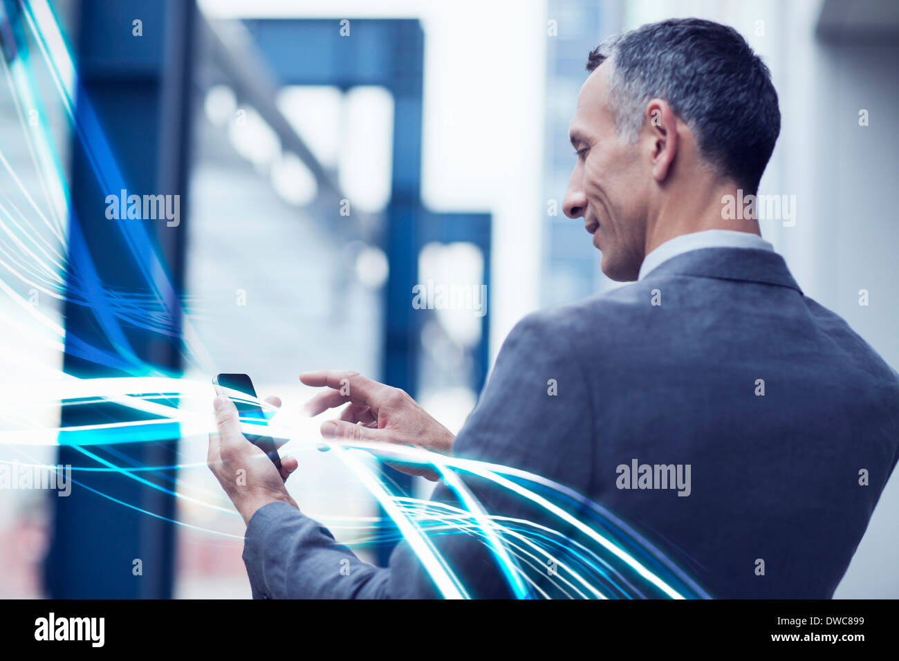 Waves of blue light and businessman using touchscreen on smartphone - Stock Image