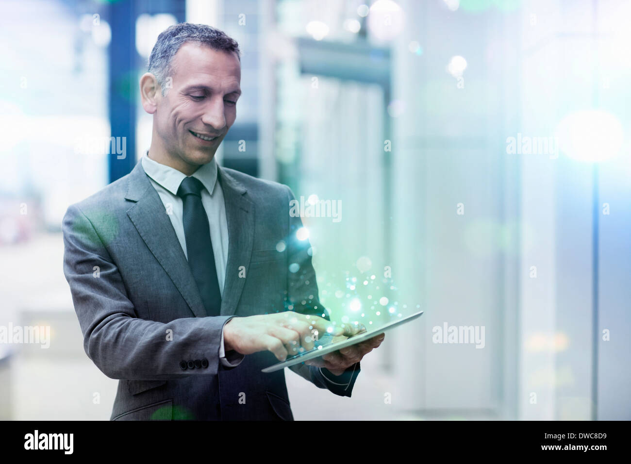 Businessman using digital tablet with glowing lights coming out of it - Stock Image