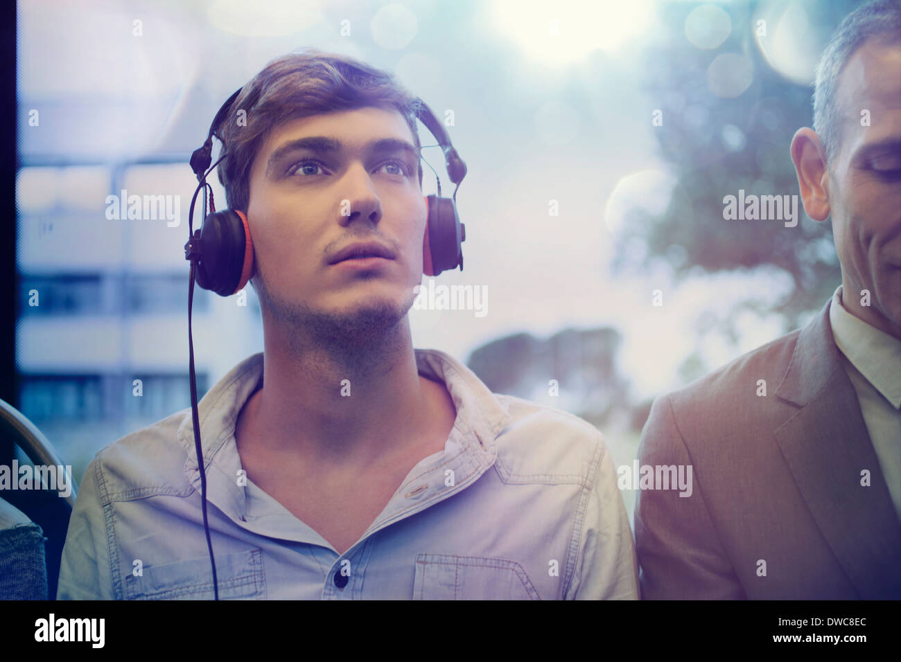Young man daydreaming and listening to headphones on train - Stock Image