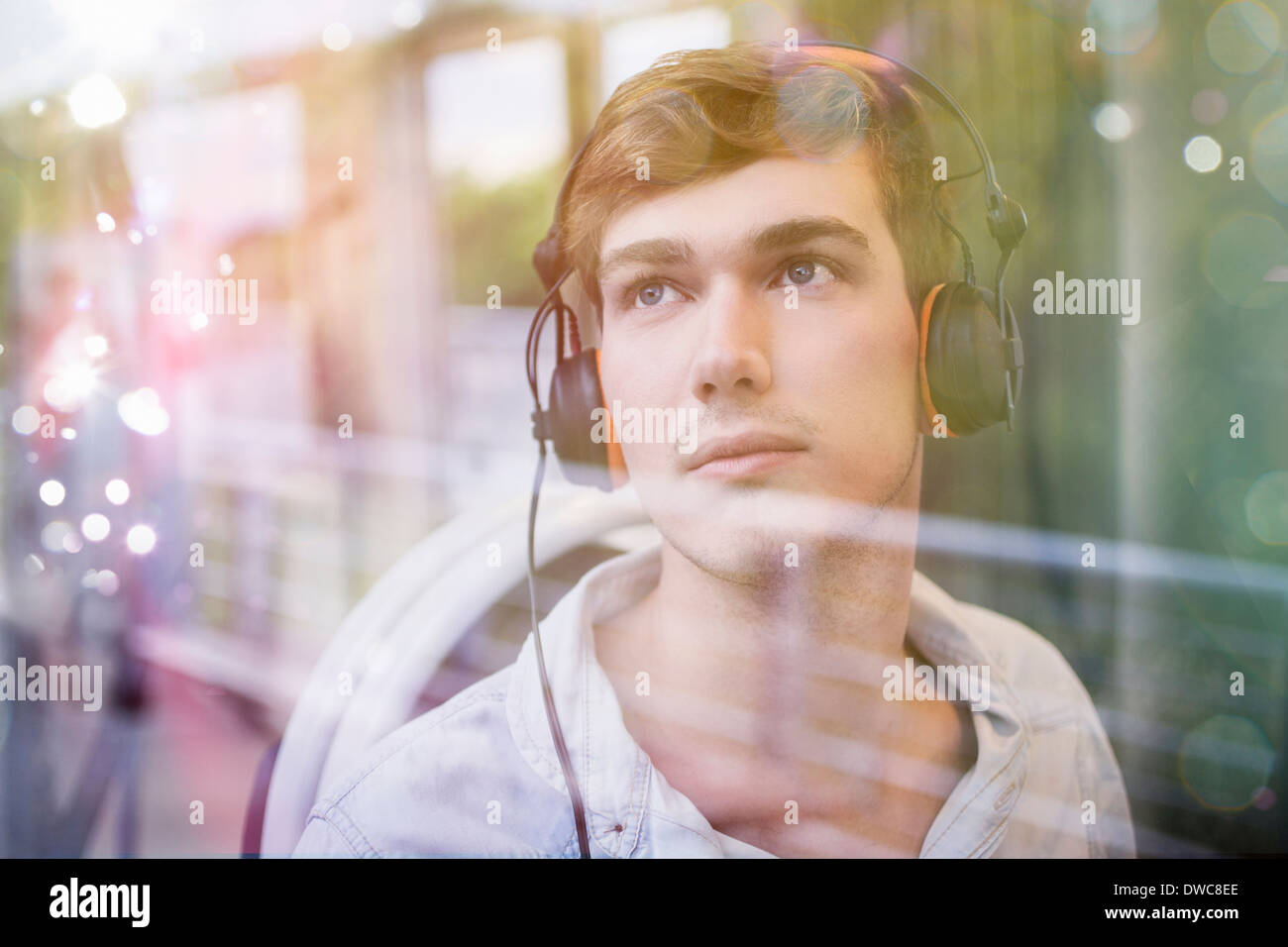 Young man on train, daydreaming and listening to headphones - Stock Image