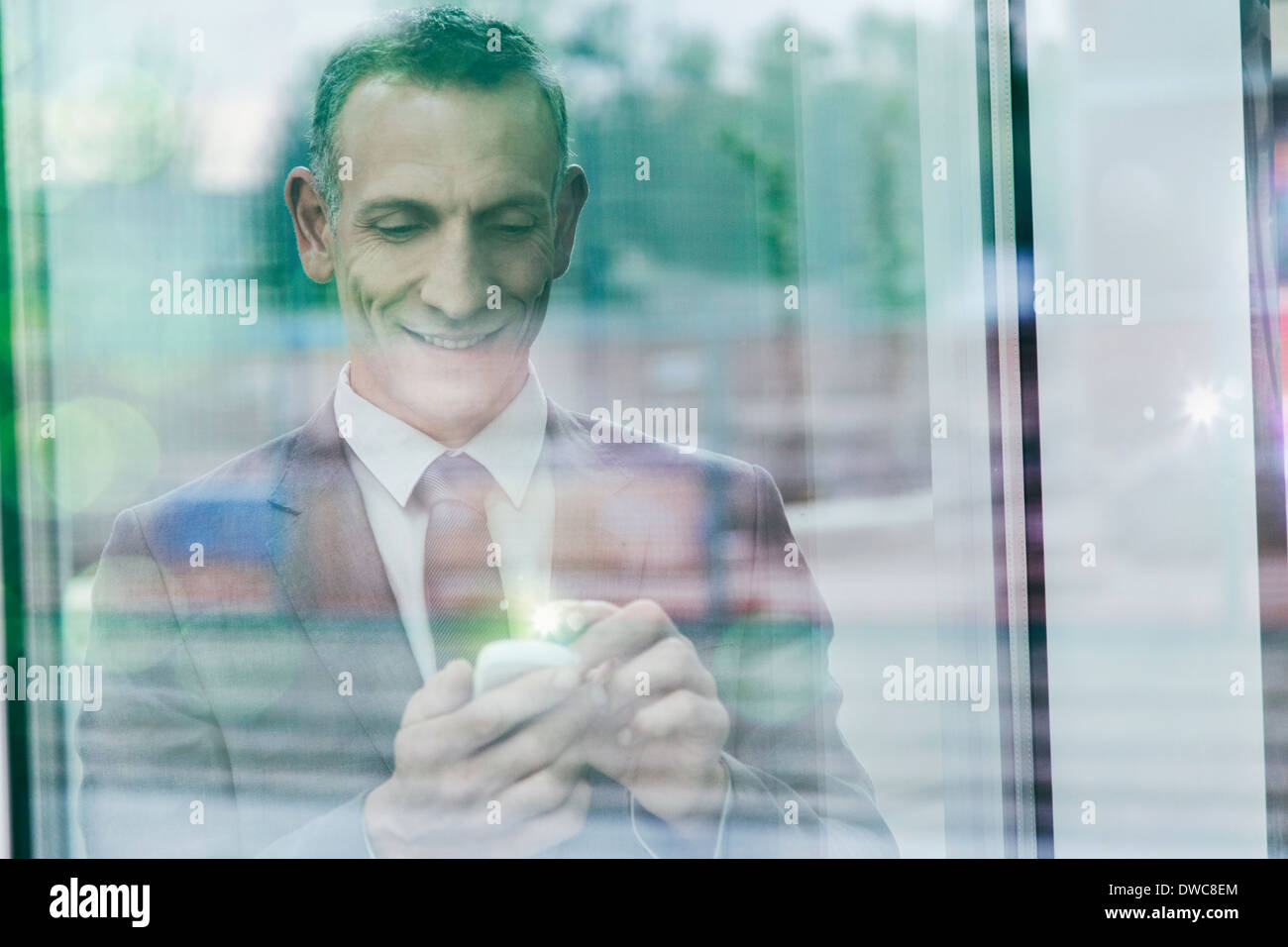 Businessman with glowing finger using smartphone touchscreen - Stock Image