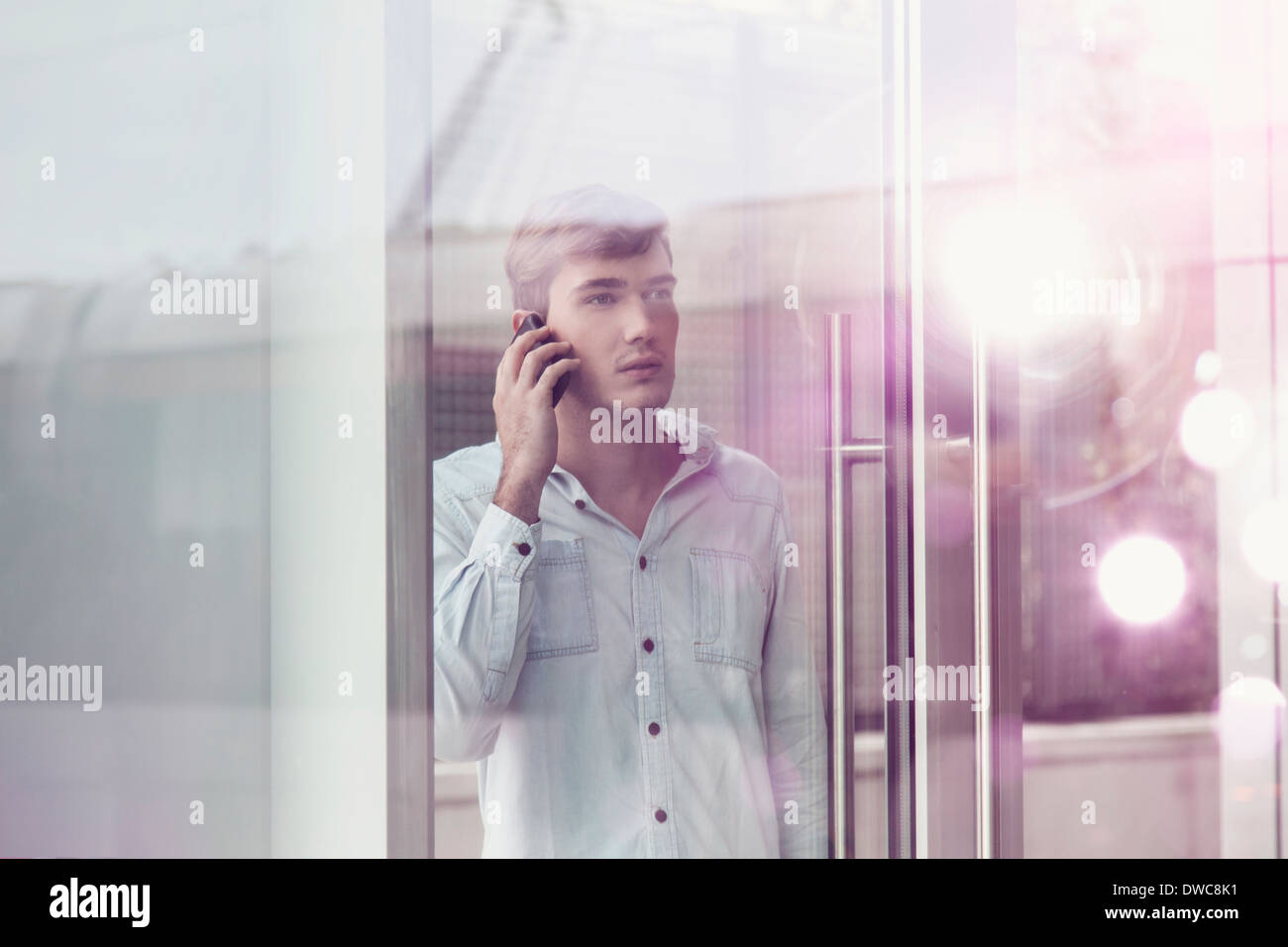 Young man behind illuminated reflective glass talking on smartphone - Stock Image