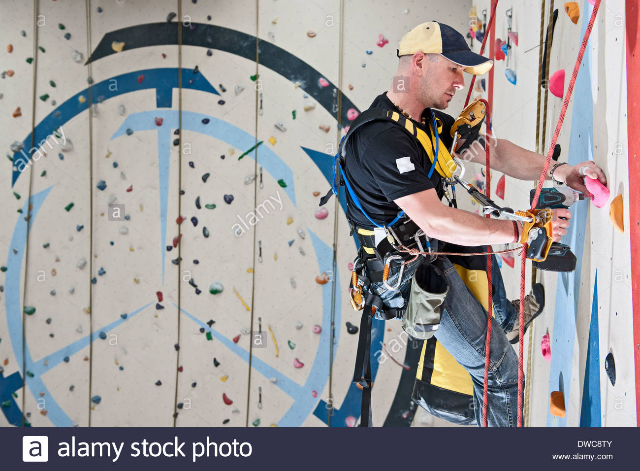 Route setter preparing new route on indoor climbing wall - Stock Image
