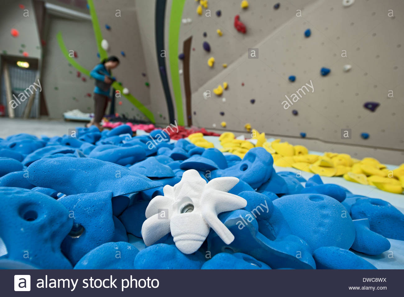 Climbing holds and woman preparing to climb on climbing wall - Stock Image