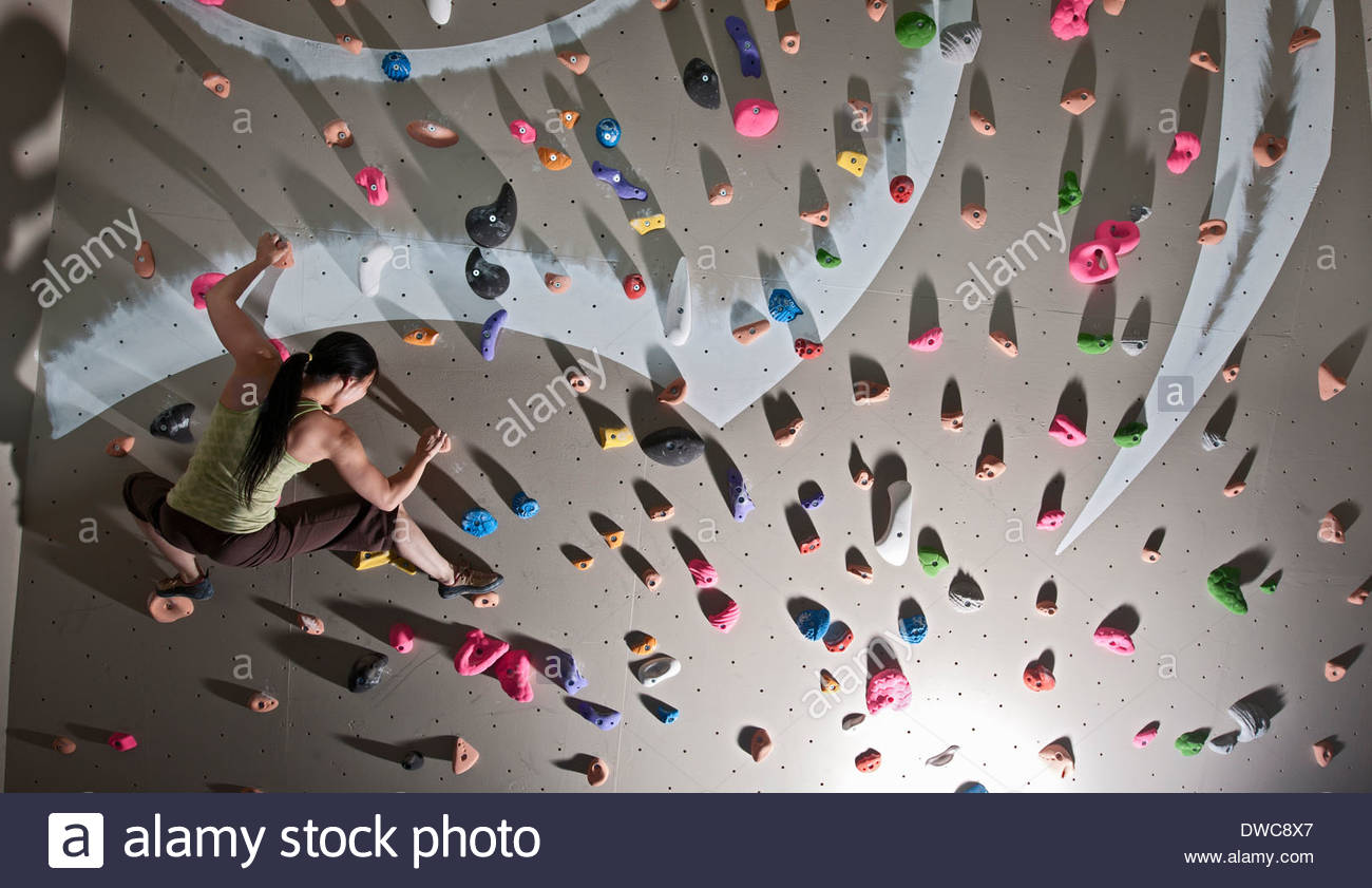 Mature woman bouldering on climbing wall - Stock Image