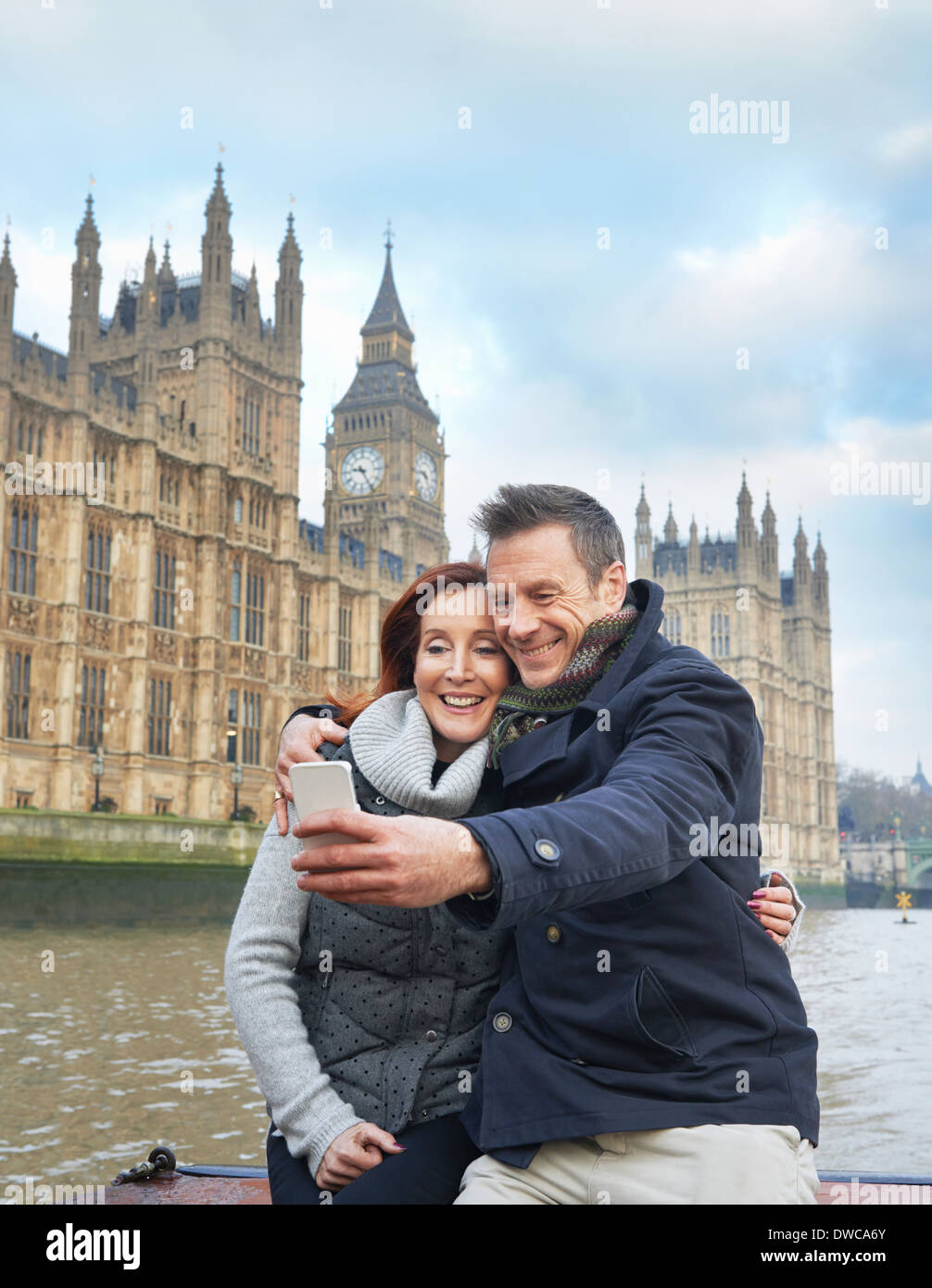 Mature tourist couple photographing selves and Houses of Parliament, London, UK - Stock Image