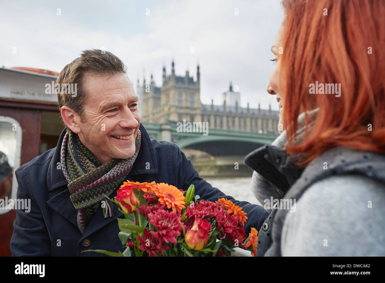 Romantic mature couple with bunch of flowers, London, UK - Stock Image