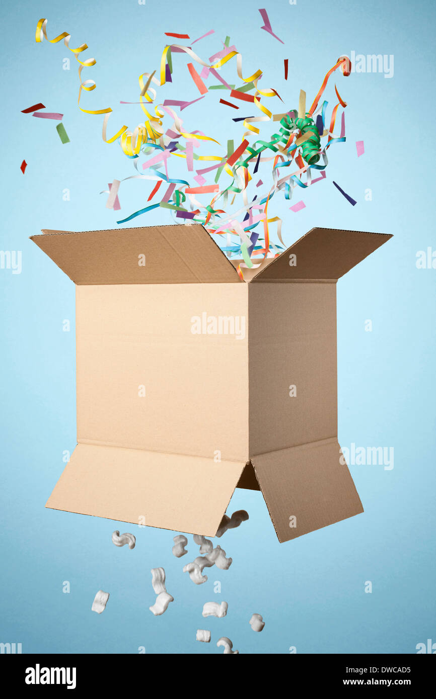 Studio shot of cardboard box with streamers exploding out - Stock Image