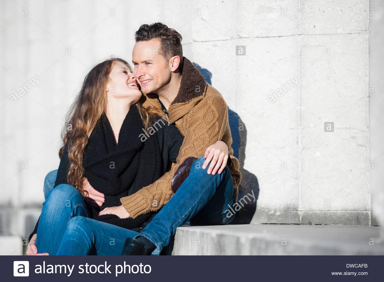 Romantic couple sitting on steps - Stock Image