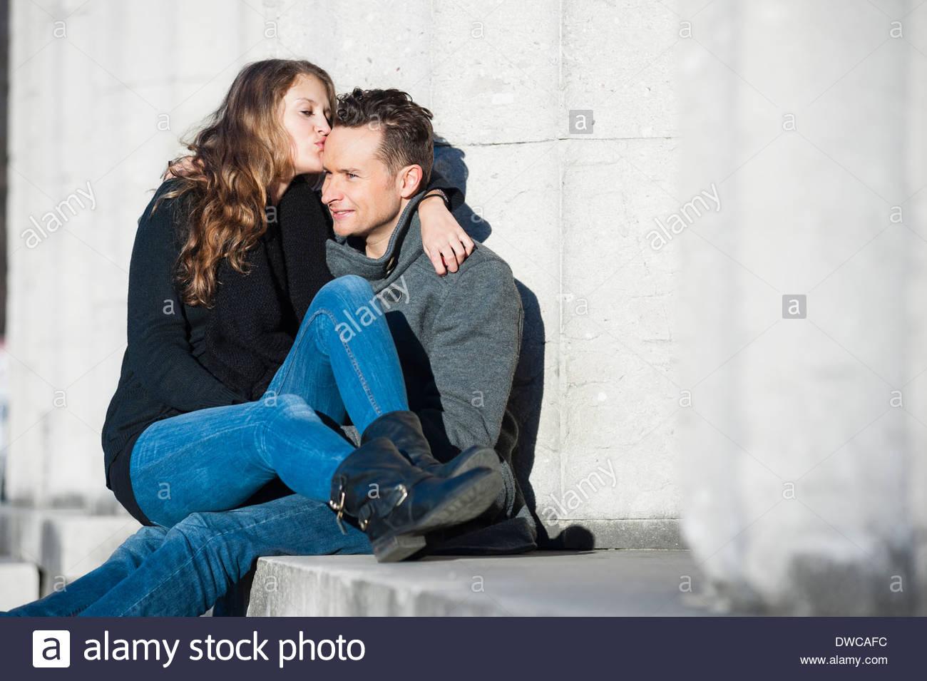 Portrait of happy couple sitting on step - Stock Image