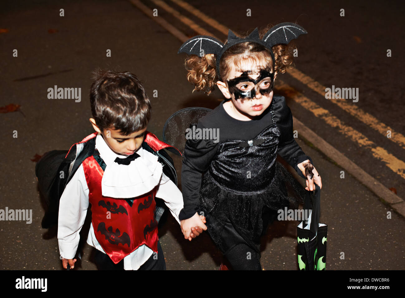 Girl and toddler trick or treating at night - Stock Image