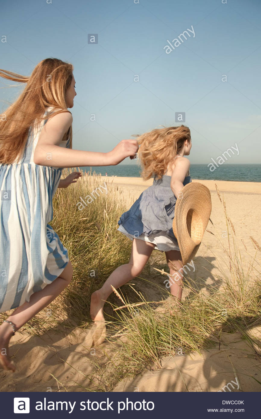 Teenage girls running to the beach, Southwold, Suffolk, UK - Stock Image