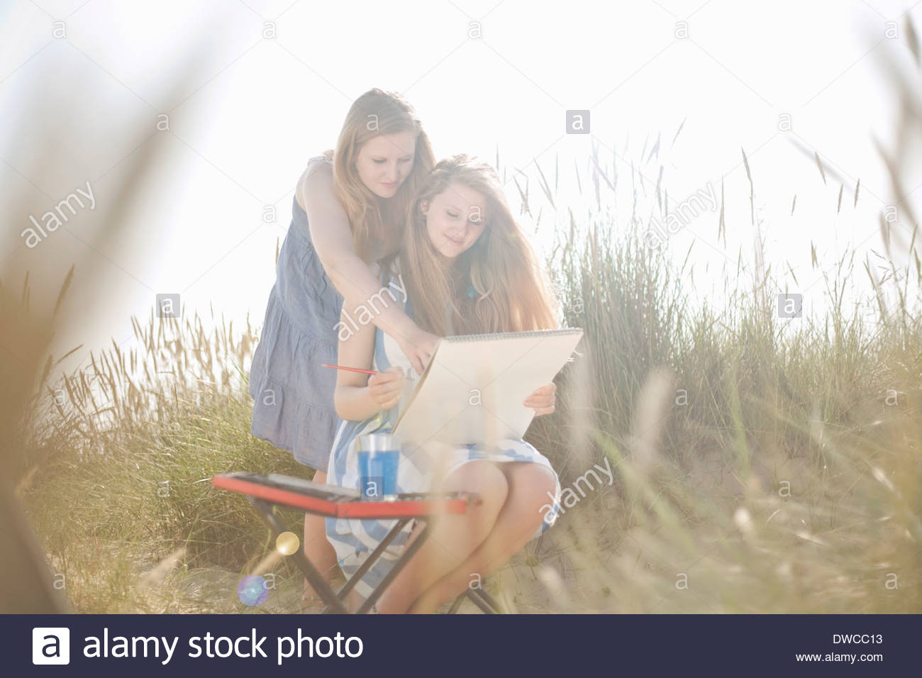 Teenage girls drawing on the beach - Stock Image