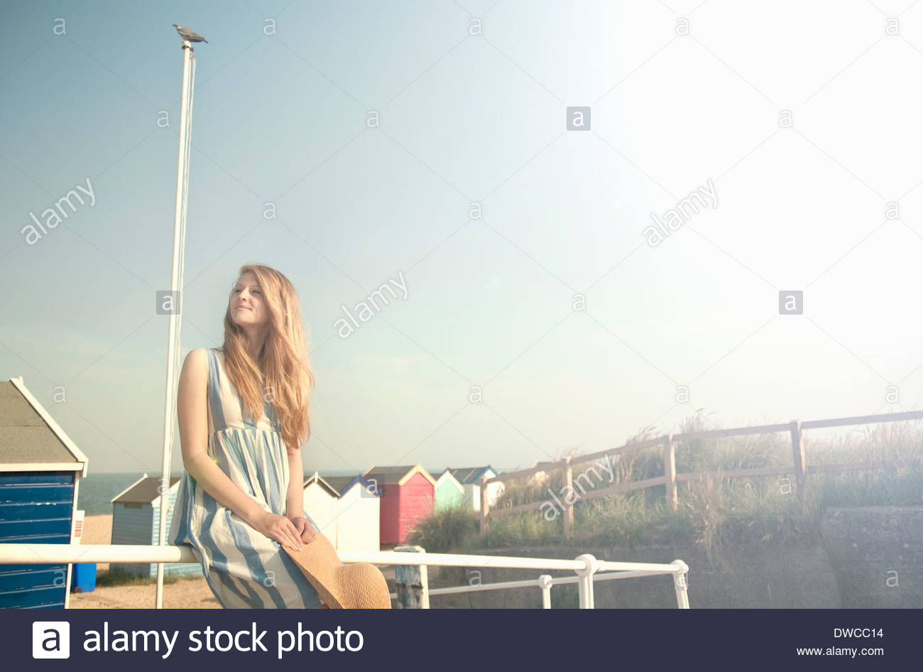 Teenage girl, beach huts in background, Southwold, Suffolk, UK - Stock Image