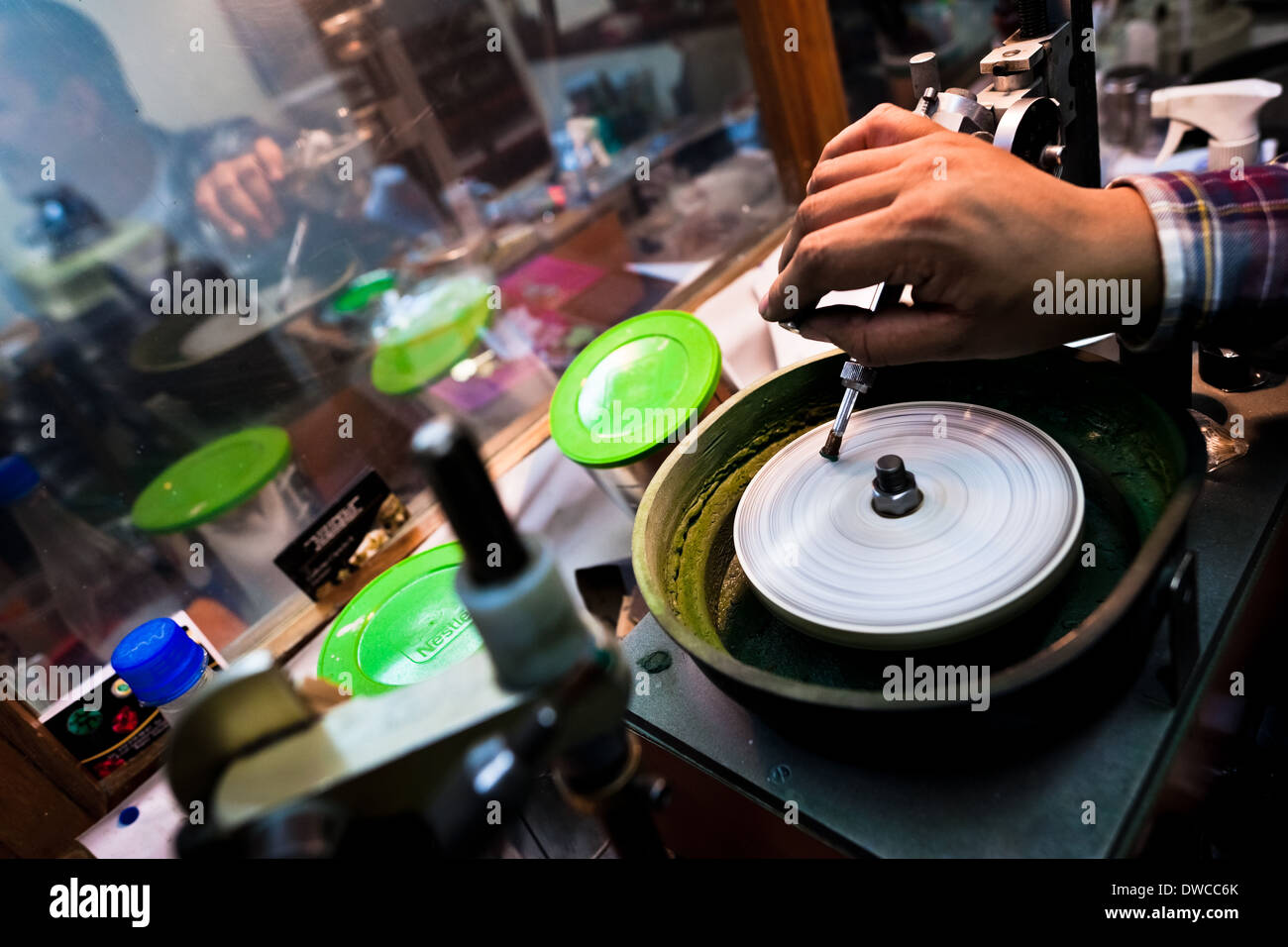 An emerald cutter polishes a gemstone in a cutting and polishing workshop in Bogota, Colombia. - Stock Image