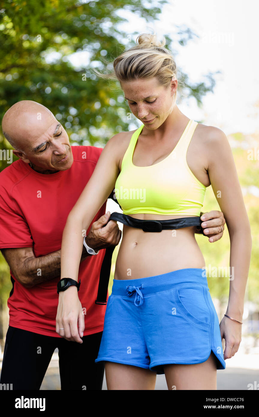 Personal trainer checking athletes heart rate monitors - Stock Image