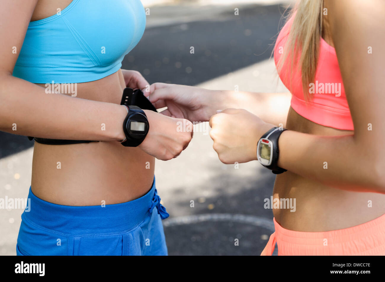 Young female athletes checking heart rate monitors - Stock Image