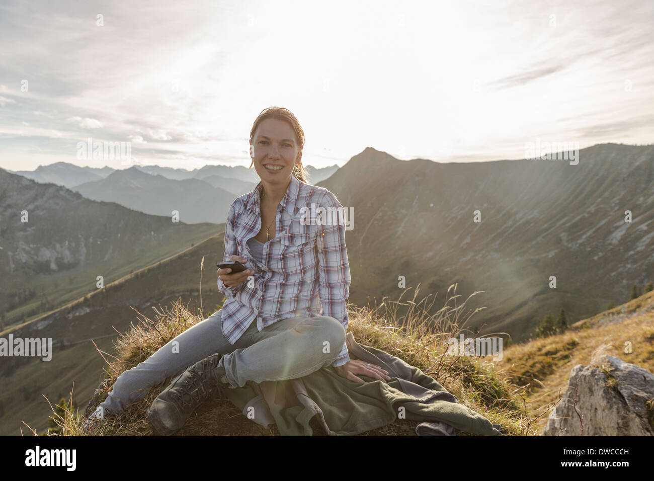 Portrait of a mid adult woman backpacker with smartphone, Achensee, Tyrol, Austria - Stock Image
