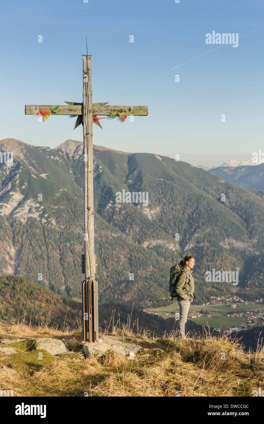 Mid adult woman backpacker and wooden cross, Achensee, Tyrol, Austria - Stock Image