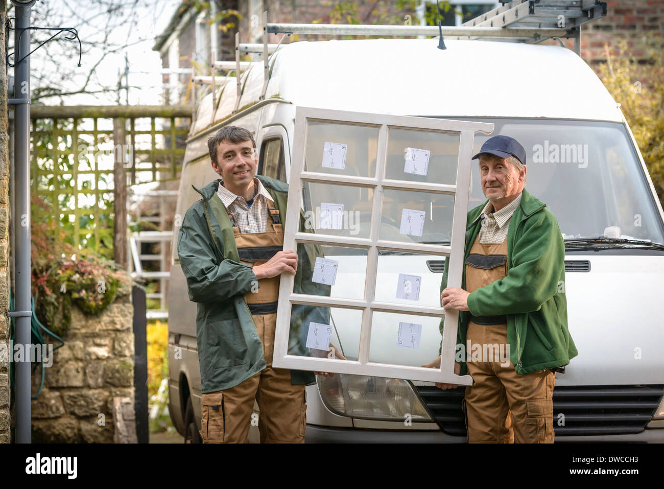 Portrait of father and son builders holding new window - Stock Image