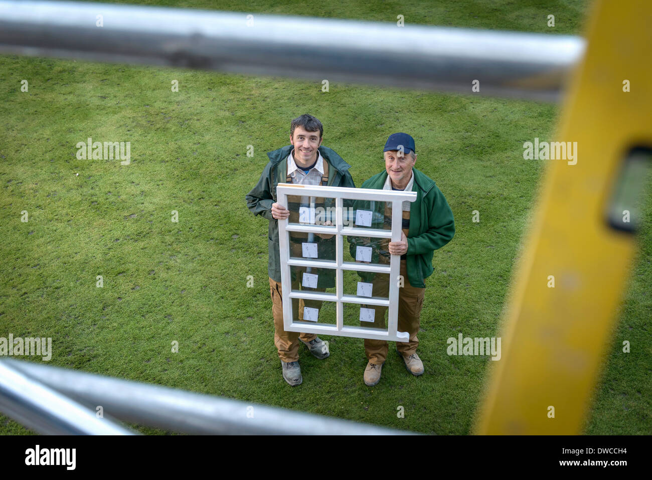 Portrait of father and son builders holding new window, high angle view - Stock Image