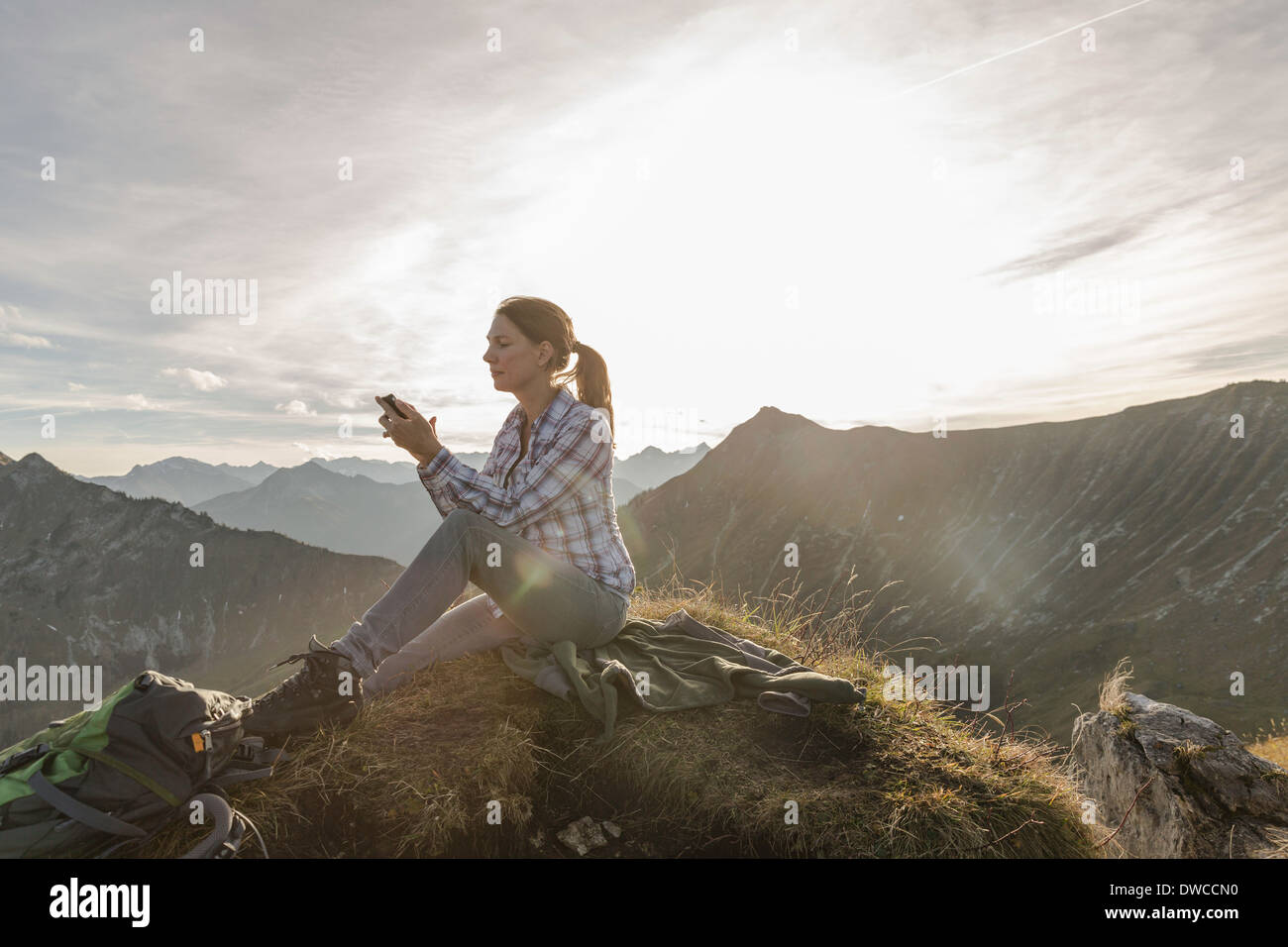 Portrait of a mid adult woman backpacker using smartphone, Achensee, Tyrol, Austria - Stock Image
