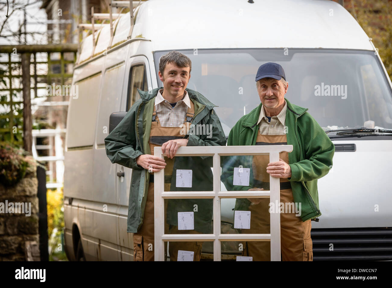 Portrait of father and son builders holding new window for installation - Stock Image