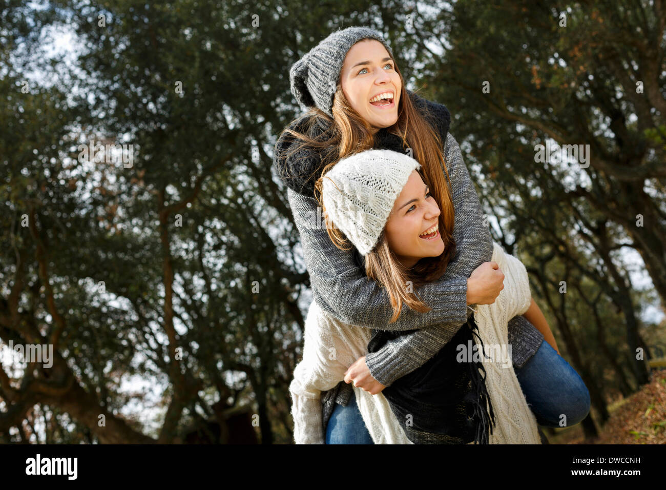 Sisters piggy back riding in forest - Stock Image