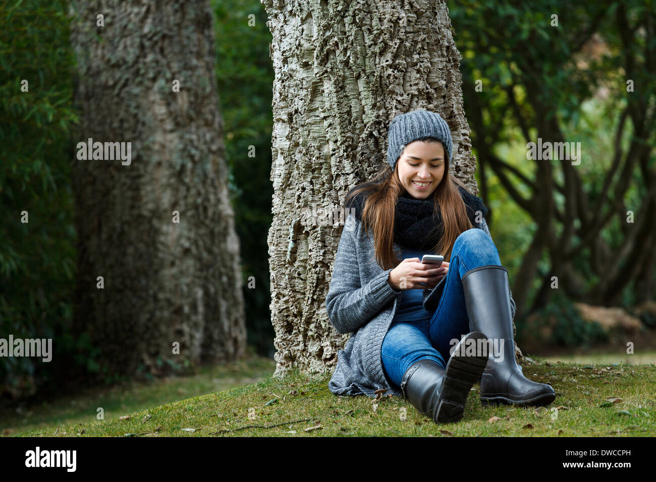 Young woman using cellular phone in forest - Stock Image