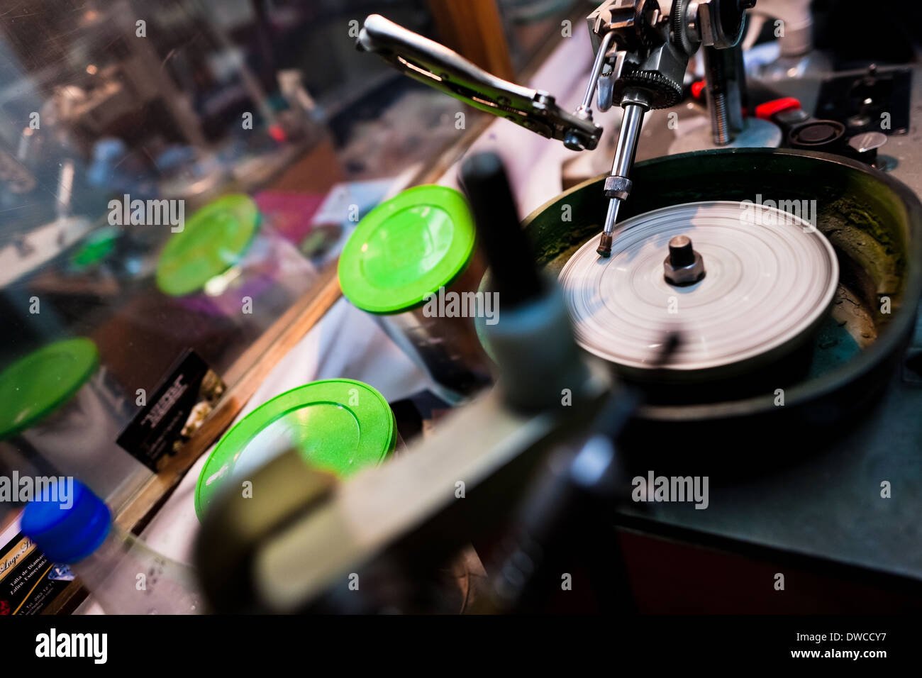 An emerald gemstone seen being polished on a machine a in a cutting and polishing workshop in Bogota, Colombia. - Stock Image