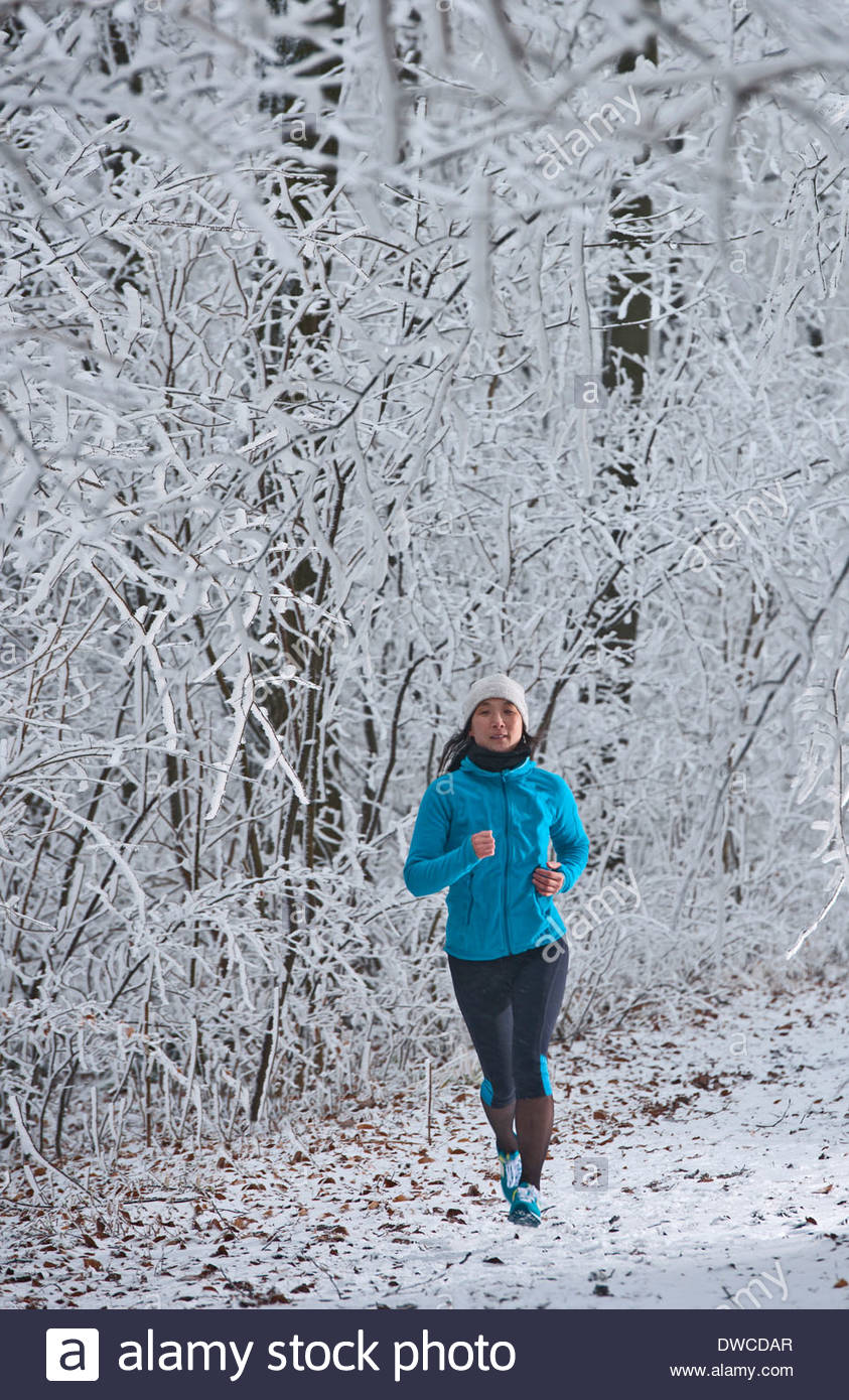 Mature woman jogging in forest in winter snow Stock Photo