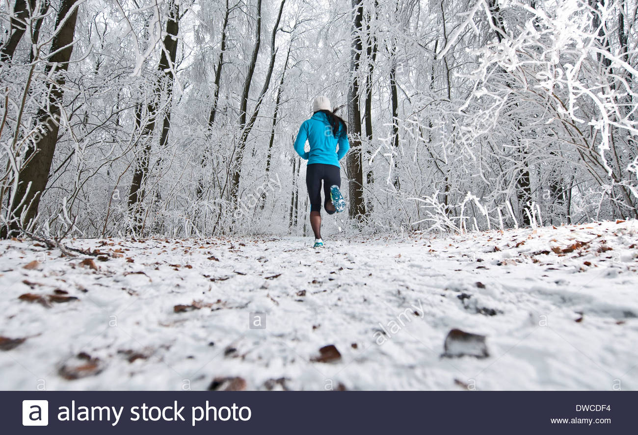 Mature woman jogging in forest in winter snow - Stock Image