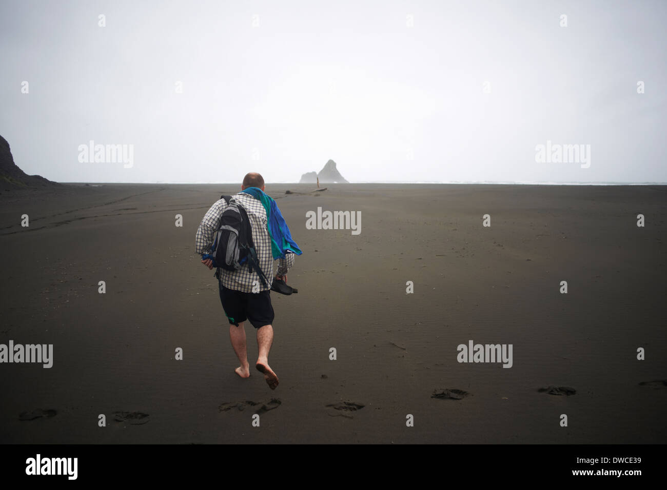 Man walking on Karekare beach, Karekare, New Zealand - Stock Image