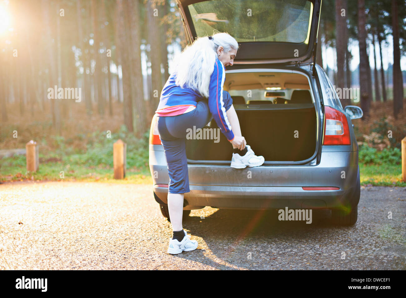 Mature woman putting on trainers on car boot - Stock Image