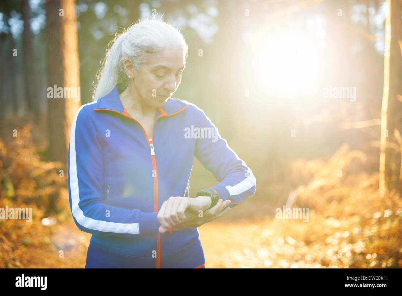 Mature woman wearing tracksuit top checking the time - Stock Image