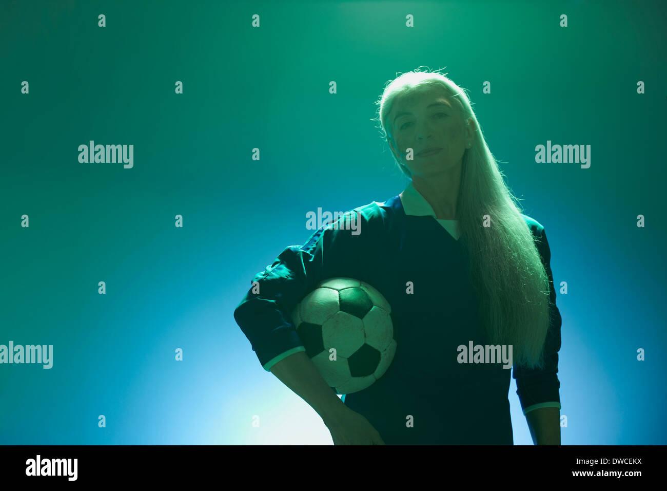 Mature woman holding football, backlit - Stock Image