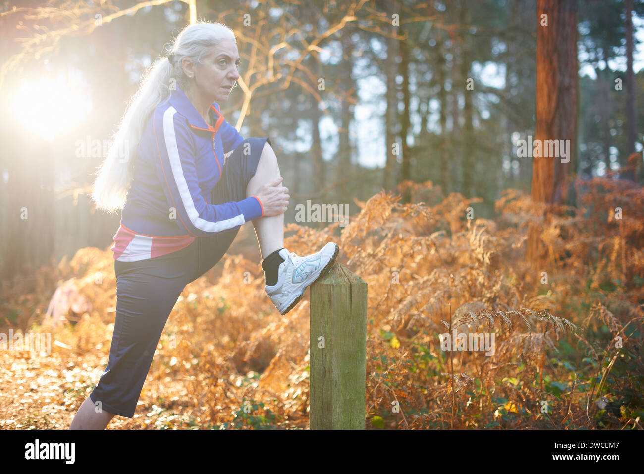 Mature woman stretching leg on wooden post - Stock Image