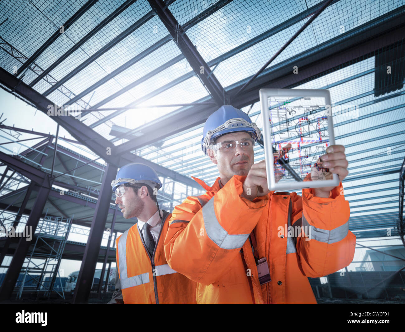 Builders working on plan details using digital tablet - Stock Image