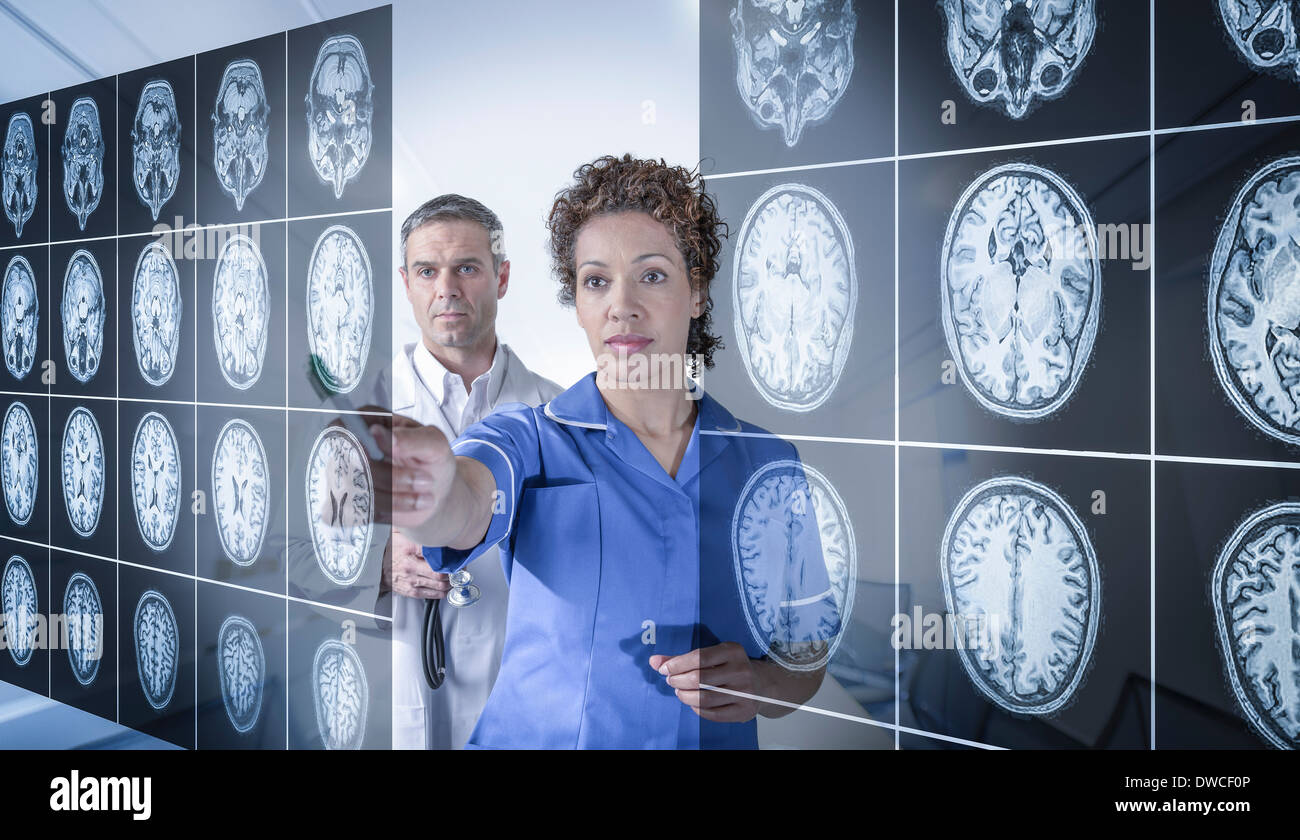 Doctor and nurse working with MRI brain scans seen through interactive display - Stock Image