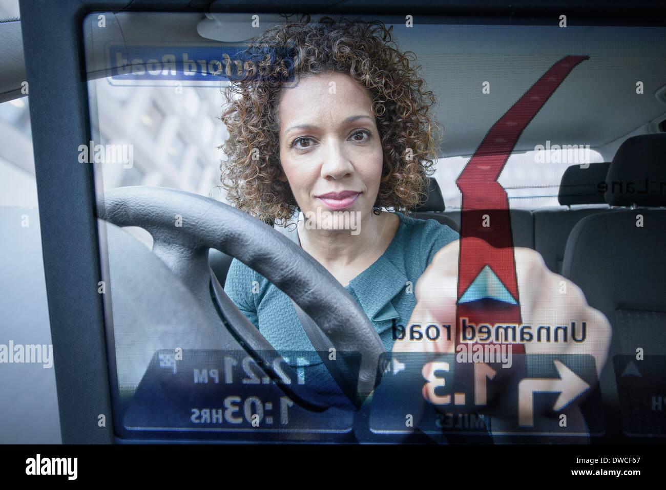 Woman operates car satellite navigation as seen through screen - Stock Image